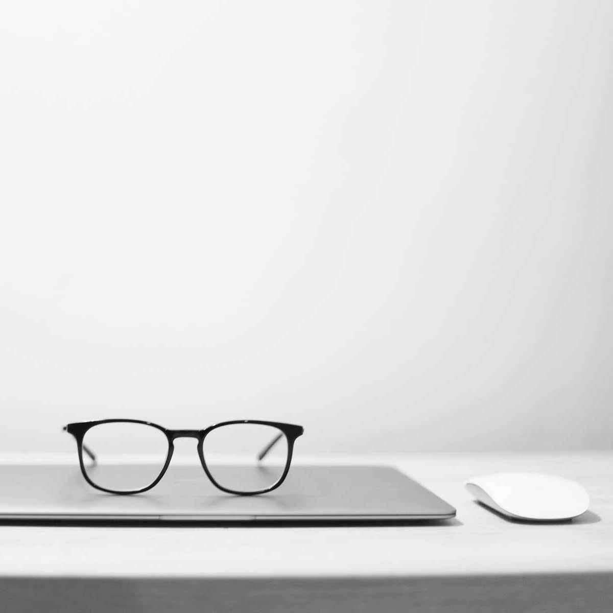 Brille Laptop Maus auf Tisch